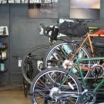Multi-colored bikes with wheels and bags by a gray brick wall in Baltimore Bicycle Works, or BBW in Belvedere Square