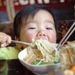 Young Asian boy eating noodles with a fork while his mother eats from the same bowl with chopsticks at Thai Landing.