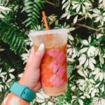 Young girl holding an iced Dunkin' coffee in front of greenery and plants.