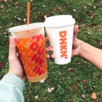 Two people holding an iced and hot Dunkin' coffee together in front of grass.